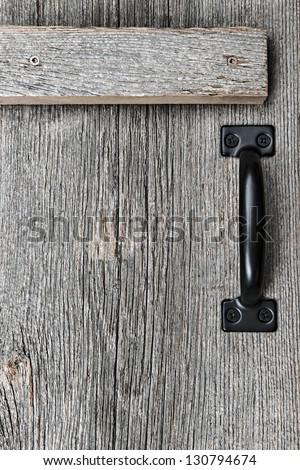Distressed rustic barn wood door with handle as textured background - stock photo