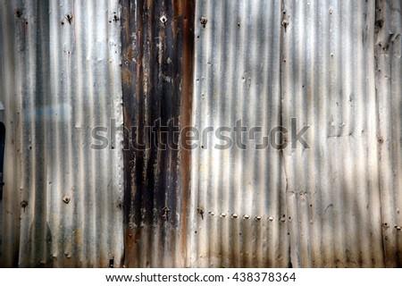 Distressed rusty corrugated iron fence background with dappled light - stock photo