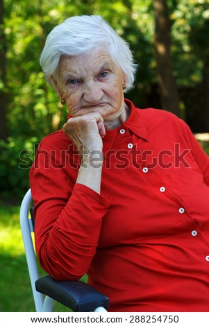 Distressed wrinkled elderly woman relaxing in the garden - stock photo