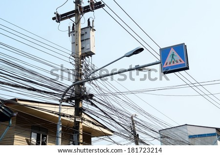 Distribution transformer  vs telephone lines/Electrical transmission lines  - stock photo