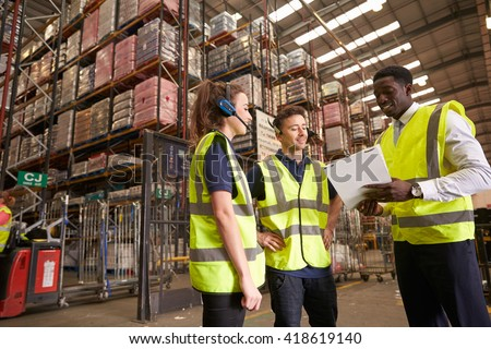 Distribution warehouse manager instructing colleagues - stock photo