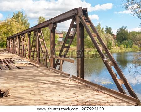 Disturbed rusty steel bridge above river in diminishing perspective. Nikolo-Uryupino village, Moscow, Russia. - stock photo