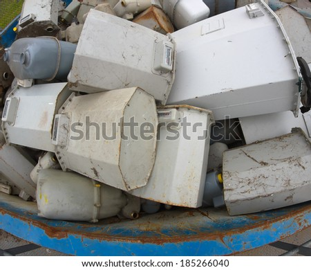 disused gas counters in a big blue container in the dump - stock photo