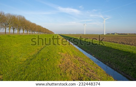 Ditch along a plowed field at sunset in autumn - stock photo