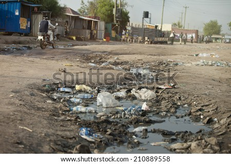 ditch full of sewage and garbage in street of South Sudan - stock photo