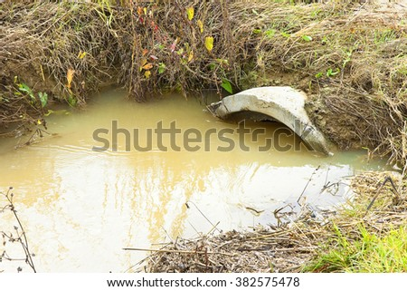 Ditch in a field after torrential rain with copy space - stock photo