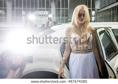 Diva stepping out of a stretch limousine, surrounded by press, paparazzi and tabloid reporters during a red carpet event