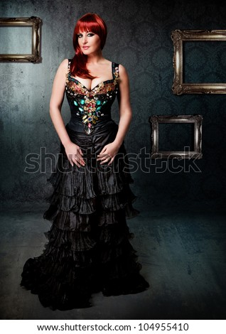 Diva with black evening-robe in front of old wallpaper - stock photo