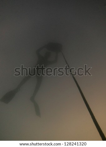 diver at buoy with a long rope in the lake - stock photo