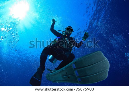 Diver do safety stop underwater - stock photo
