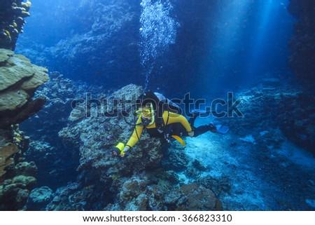 diver exploring a cave - stock photo