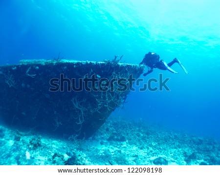 diver exploring a wreck - stock photo