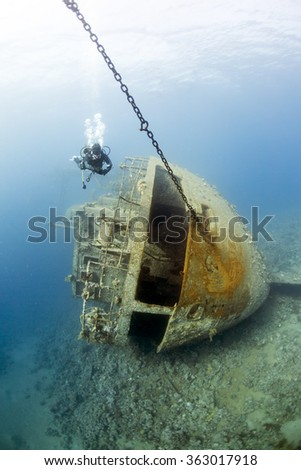 Diver swims over the ship wreck, Aqaba, Red Sea, Jordan - stock photo