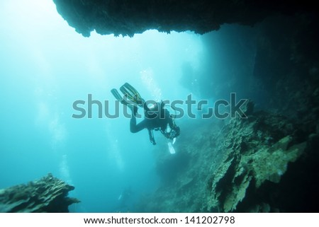 diver undersea pass through cave