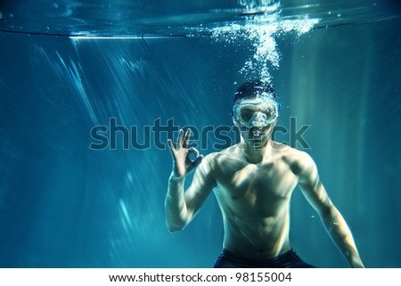 Diver underwater showing ok sign isolated on blue background - stock photo