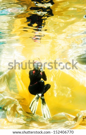 diver underwater with golden background - stock photo