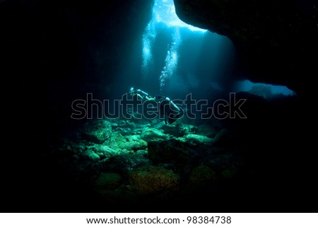 Divers exploring a Lava Tube in South Kona Hawaii - stock photo