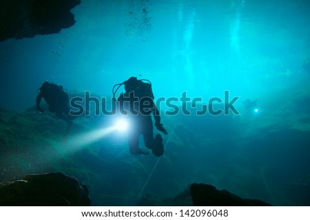 Divers in cenote - stock photo