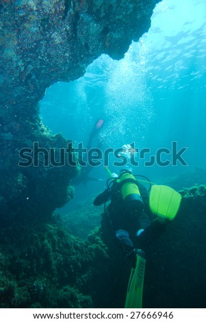 Divers in the mediterranean sea on a cave`s exit.