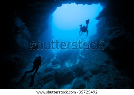 divers in underwater cave - stock photo