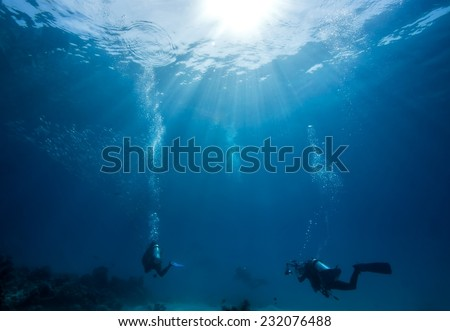 Divers passing coral reef under beautiful sun ray in Dimakya Island, Palawan.