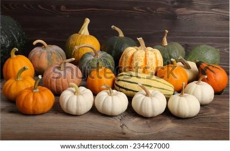 Diverse assortment of pumpkins on a wooden background. Autumn harvest. - stock photo