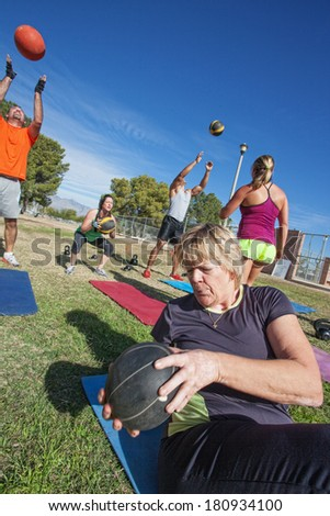 Diverse boot camp fitness class exercising outdoors - stock photo