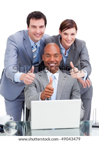 Diverse business co-workers with thums up at a laptop in the office