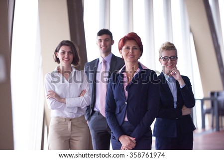 diverse business people group standing together as team  in modern bright office interior  with redhair senior woman in front as leader - stock photo