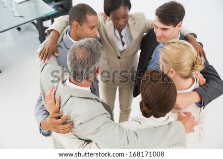 Diverse business team hugging in a circle in the office