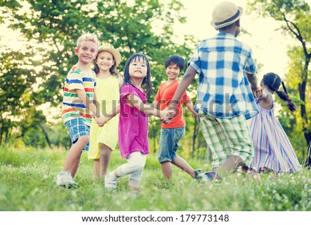 Diverse Children Holding Hands and Dancing in The Park - stock photo