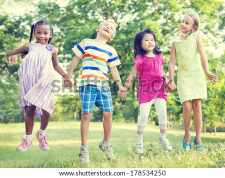 Diverse Children Jumping Together in a Park - stock photo