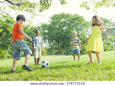 Diverse Children Playing Ball in The Park - stock photo