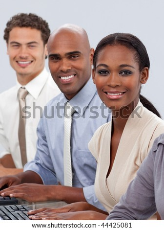 Diverse confident business team sitting in a row smiling at the camera