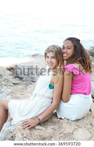 Diverse friends, caucasian and african american teenager girls sitting together on textured rocks turning looking at camera, smiling by the sea, outdoors nature. Healthy holiday lifestyle, exterior. - stock photo