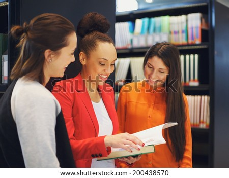 Diverse group of college students in library reading a book together. Female students looking for information in reference books for their studies. - stock photo