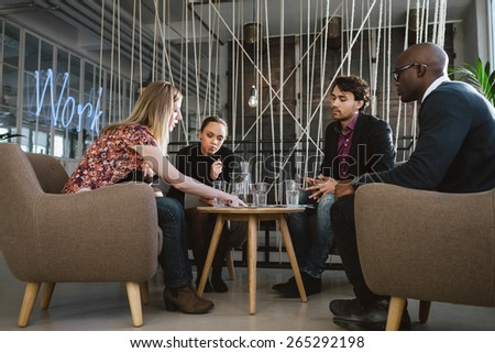 Diverse group of executives meeting in office sharing creative ideas. Young people having a meeting in lobby with woman showing something to coworkers. - stock photo