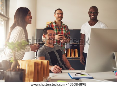 Diverse group of four Black, Hispanic and Caucasian young adult entrepreneurs together in front of computer monitor on desk at small business office - stock photo