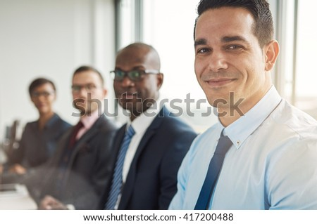 Diverse group of four grinning attractive business people sitting at table with back to large bright office window with light flare - stock photo