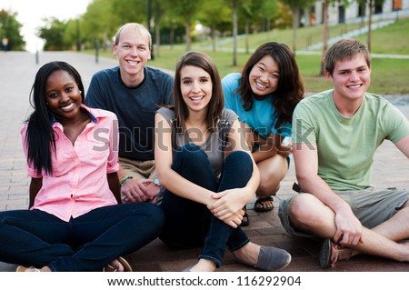Diverse group of friends outside smiling together - stock photo