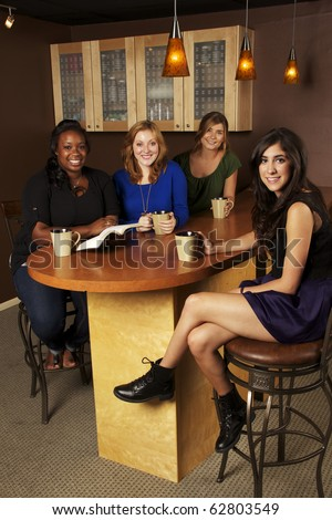 Diverse group of Girlfriends reading the Bible at a Cafe