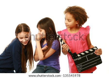 diverse group of girls with one whispering and other holding film slate - stock photo