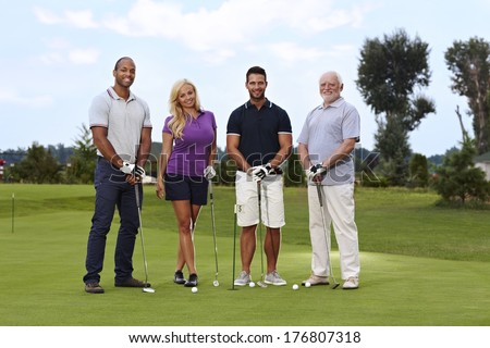 Diverse group of golfers standing on the green, smiling, looking at camera. - stock photo