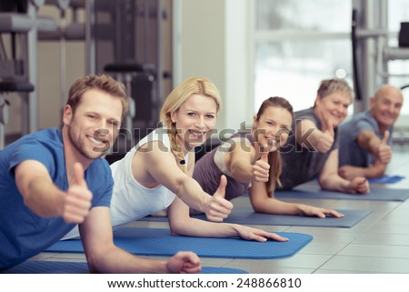 Diverse group of happy healthy people exercising at a gym on their exercise mats all looking at the camera giving a thumbs up of approval