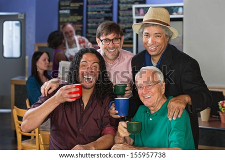 Diverse group of men celebrating in coffee house - stock photo