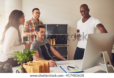 Diverse group of multi-ethnic young adult business people assembled around desk looking at something on their computer monitor - stock photo
