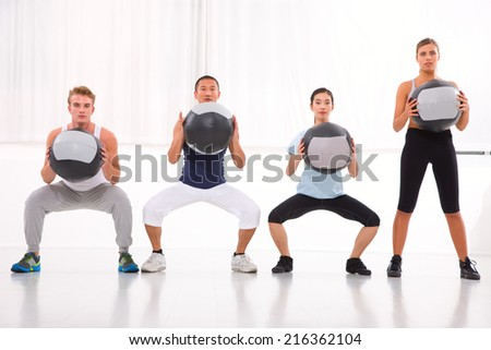 Diverse group of people exercising with pilates in gym - stock photo