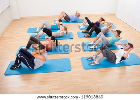 Diverse group of people working out in a gym lifting their heads with hands clasped behind to strengthen their abdominal muscles - stock photo