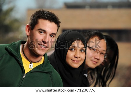 Diverse Group of Students smiling with college campus on the background - stock photo