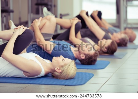 Diverse group of young and older people exercising at the gym doing leg flexes as they lie on their backs on their mats in a receding row, focus to an attractive young blond girl in the foreground